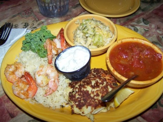 Barbara Jean's is known for their famous crab cakes. This is the crab cake and grilled shrimp over rice dinner with stewed tomatoes and broccoli & cheese casserole.