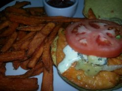 The buffalo chicken sandwich is topped with a cold tomato slice and ranch dressing.