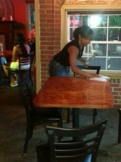 A waitress preps a table for arriving guests.