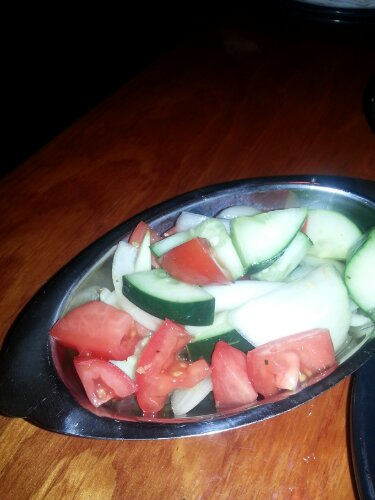 Tomato salad with cucumbers and raw onion.