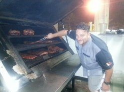 The owner, Kyle, otherwise known as Boss Hawg shows off the ribs and chicken cooking in the smoker.