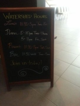 Serving brunch, lunch and dinner, the restaurant's hours are written on a stand alone chalkboard.