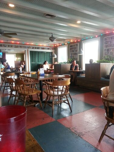 Seating includes booths and tables with checkered flooring.