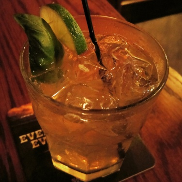 A local ginger bourbon + honey basil cocktail is garnished with fresh lime and a basil leaf.