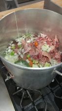 Chicken bones combine with water, a standard mirepoix and a sachet d'Epices to make chicken stock.