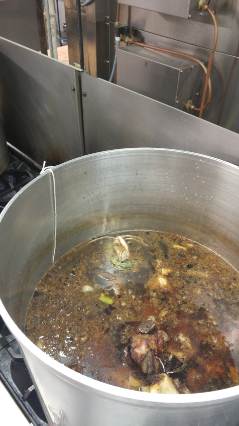 Veal stock simmers on the stovetop.