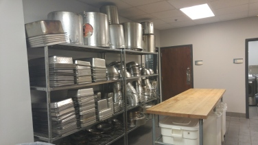 Hotel size pots and pans, along with flour stored under the butcher block table.