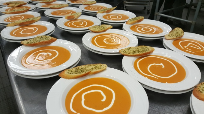 The final product: 250 portions of Tomato Bisque garnished with cream and served with garlic crostini.